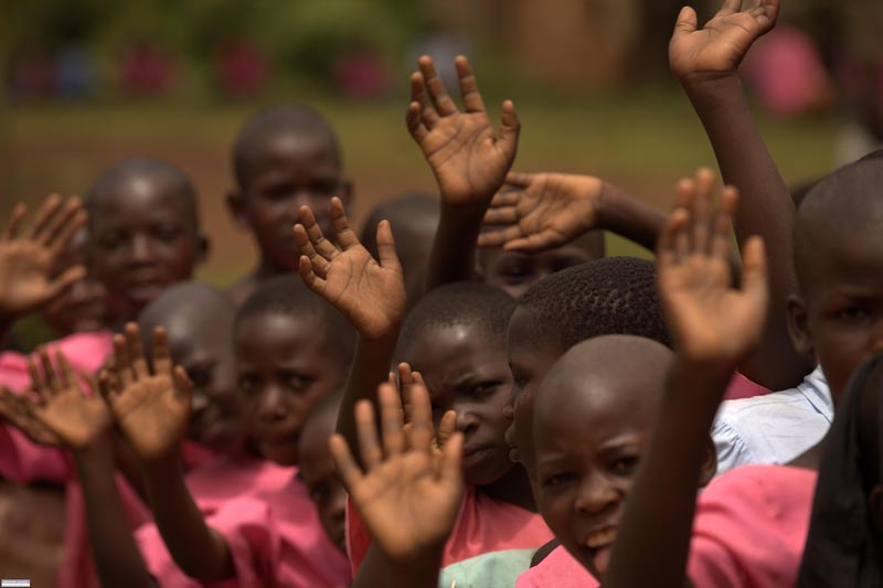 School children wave their goodbye's to the visiting Pfizer team in Iganga