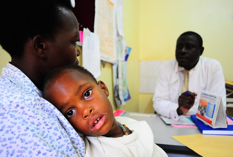 A child HIV positive is distracted as the mother consults with the doctor at Mengo hosipital