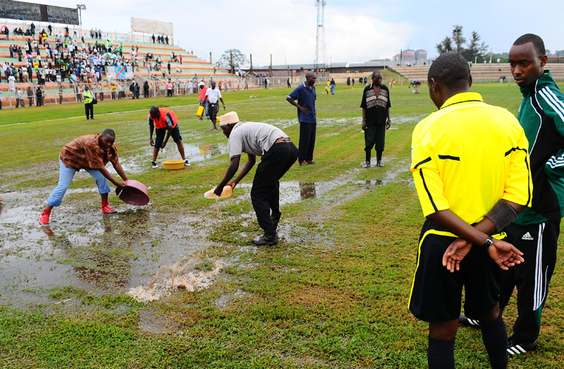 Match officials look on as Victors fans scoop out water from the playing field