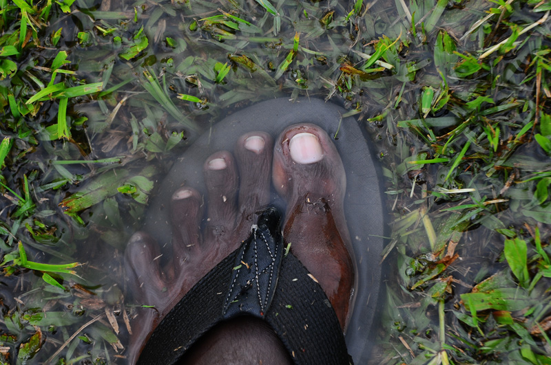 A foot submerged in water at Nakivubo stadium