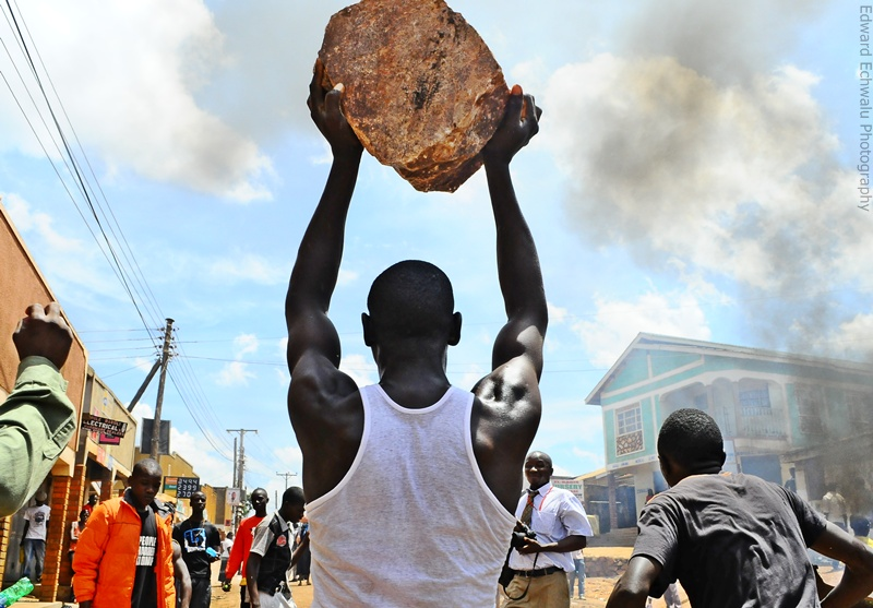 A demonstrator carries a stone to block a road during a protest against the arrest of opposition leader Kizza Besigye in Kireka suburb of the capital Kampala, April 18, 2011.