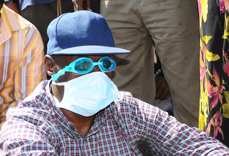 Kizza Besigye is seen wearing swimming specs as police fired teargas to disperse a crowd that was escorting him to his home