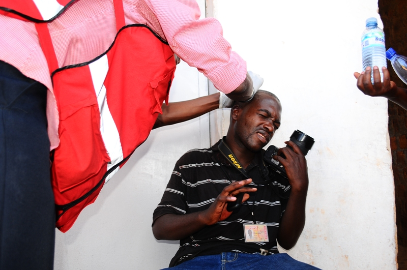 Michael Kakumirizi, a photojournalist is dressed by a Red Cross doctor after sustaining a cut on his head when police clashed with protestors in Kasangati