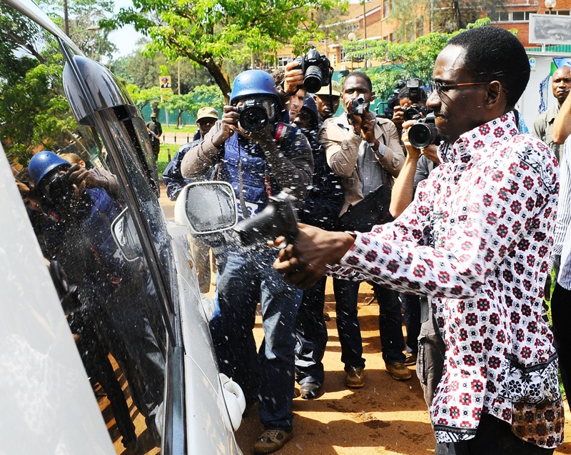 Gilbert Arinaitwe from the Elite Brigade (not formal) of the Uganda Police smashes the windscreen of Kizza Besigye's car with the butt of a pistol before arresting him on April 28, 2011