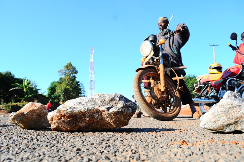A motor cyclist makes a u-turn after find the Kasangati road blocked by protestors