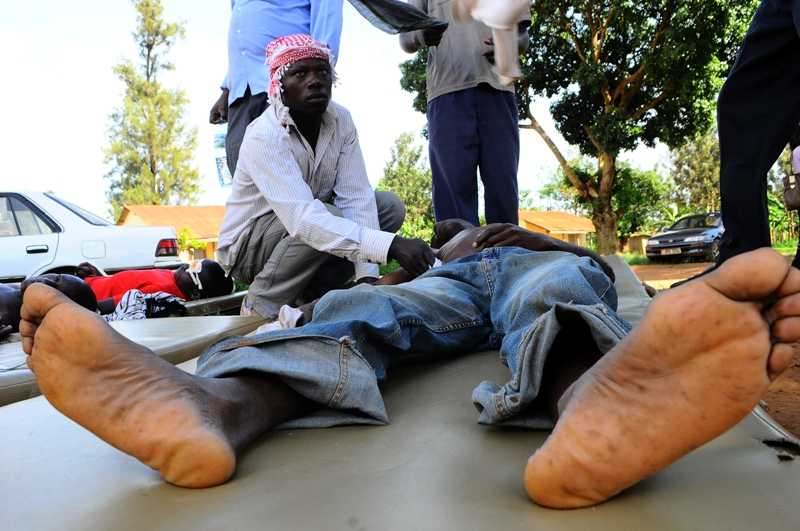 A civilian takes care of another injured by a teargas canister during the walk to work protest in Kasangati suburb of the capital, Kampala by opposition leader for Forum for Democratic Change (FDC), Kizza Besigye on April 15, 2011