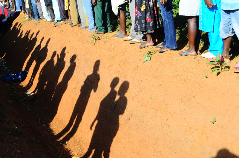 Shadows are cast of curious supporters eager to have a look at opposition leader, Kizza Besigye who was standing inside a trench after being stopped from walking to work as he continues to protest the rising food and fuel on April 15, 2011