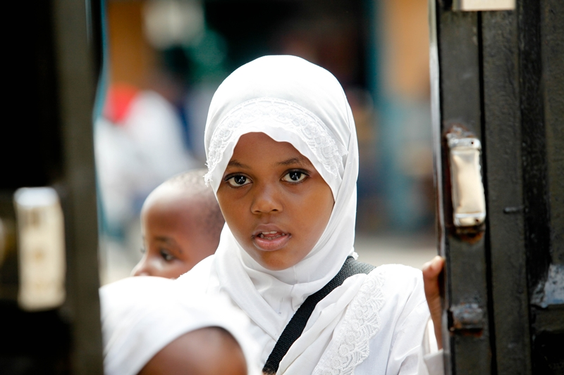 A school girl curiously looks through a gate in Ngeta, Dar es salaam