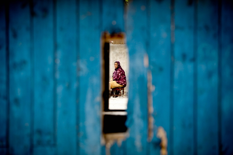 A woman is seen through a damaged door in Ngeta, Dar es salaam