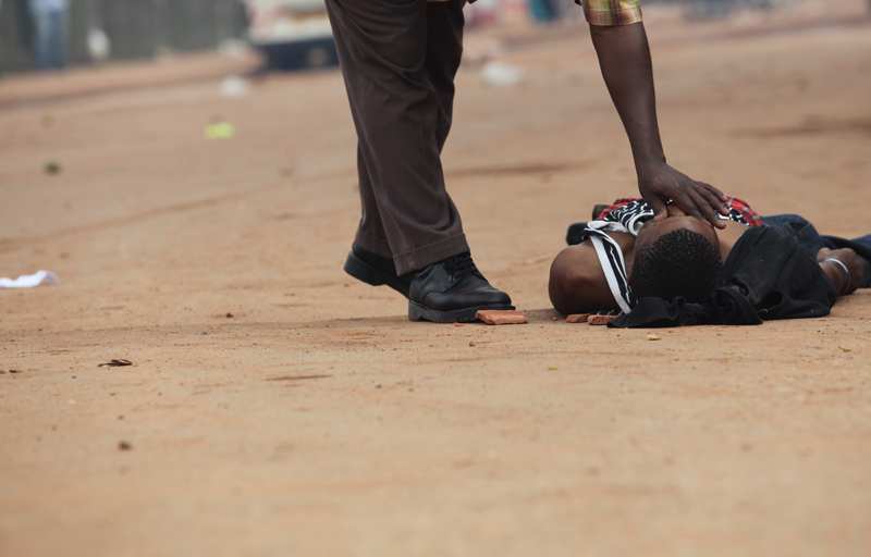 I watched a soldier spray bullets into Owino. A minute later, his random target had got this trader in the stomach. He died instantly. A fellow trader is seen closing his eyes.