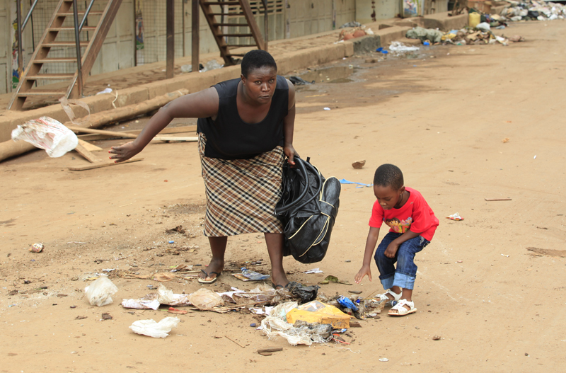 A mother and her child are forced by military Police to clear a road littered with barricades