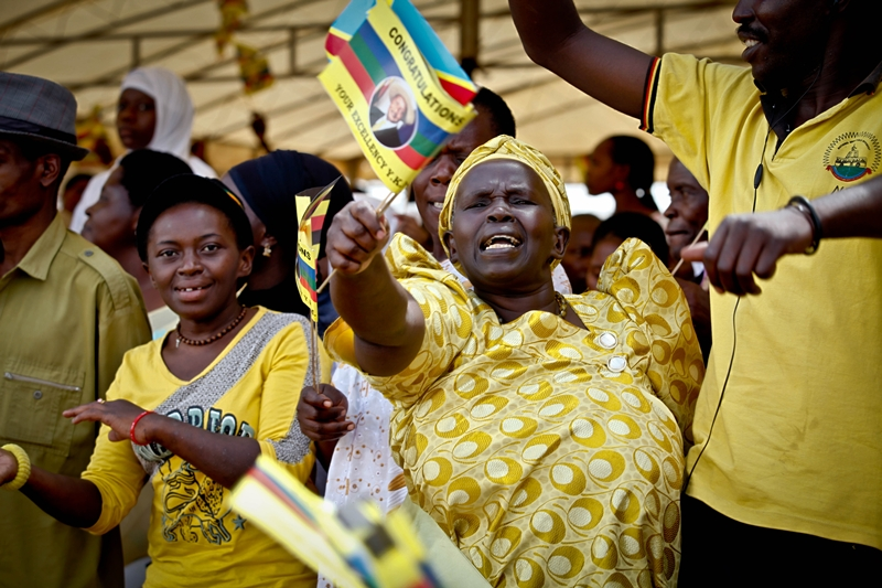 An overly excited woman waves a flag bearing President Museveni's picture moments after swearing in at Kololo Airstrip on May 12, 2011.
