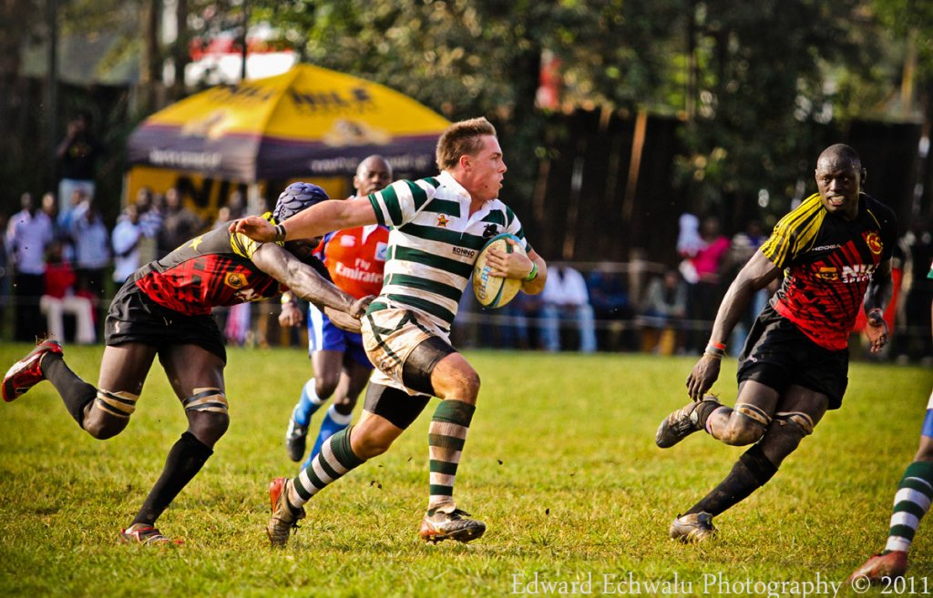 A Zimbabwean Rugby player runs past Ugandan players at Kyadondo Rugby Grounds in the opening game of Group 1B of the Confederation of African Rugby (CAR) which also includes Madagascar on June 12, 2011. Uganda lost the game 15-25.