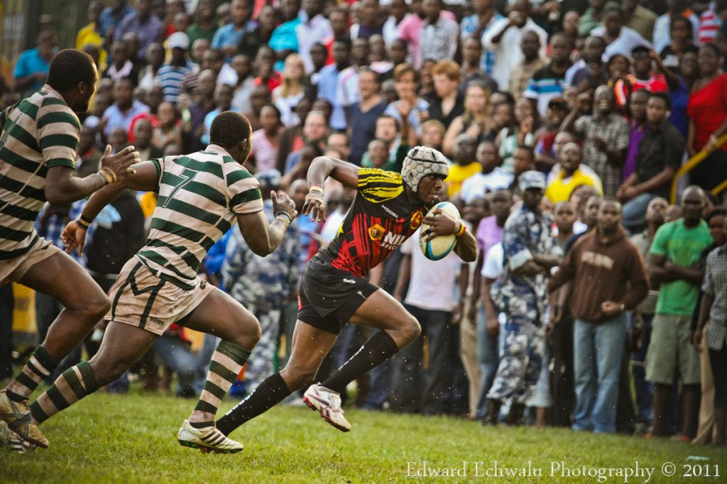 A Ugandan Rugby player runs past Zimbabwean players at Kyadondo Rugby Grounds in the opening game of Group 1B of the Confederation of African Rugby (CAR) which also includes Madagascar on June 12, 2011. Uganda lost the game 15-25.