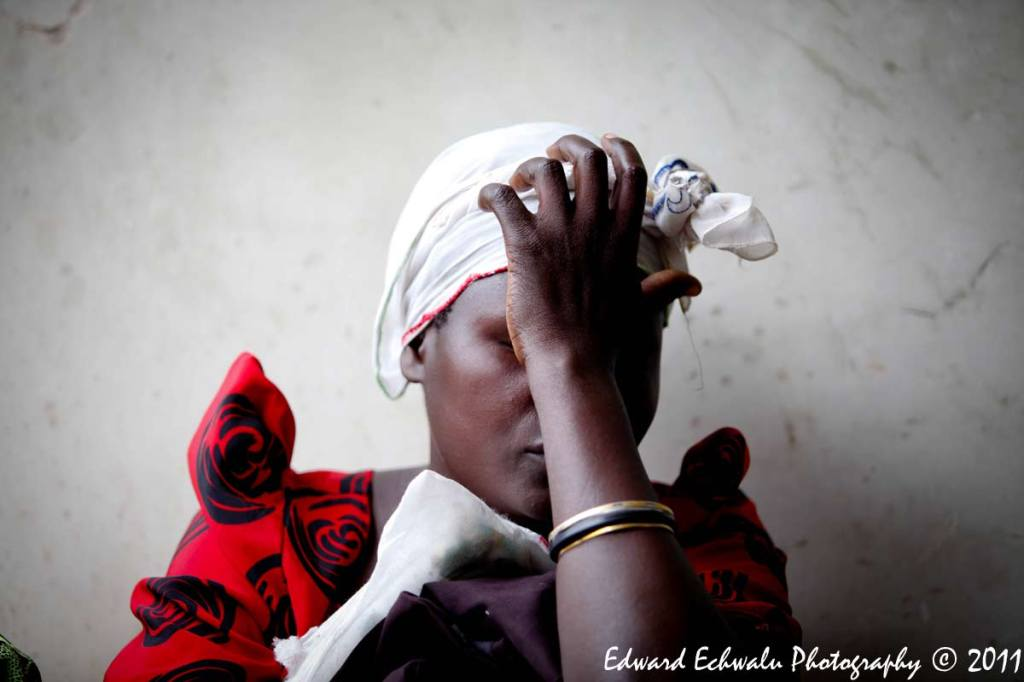 INCONSOLABLE: A mother who lost a daughter waits to take her remains from Kiryandongo Hospital morgue 210 km (130 miles) north of Uganda's capital Kampala, June 29, 2011. The lightning strike killed 18 children and their teacher. Uganda has one of the highest rates of lightning strike deaths in the world and its capital Kampala has more days of lightning per year than any other city, according to the World Meteorological Organization.