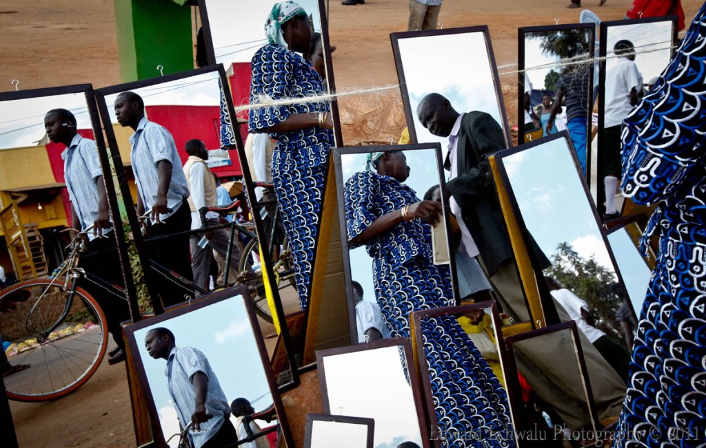 A pilgrim negotiates for dressing room mirrors by the roadside near Namugongo shrine during the Martyrs' day celebrations on June 3, 2011