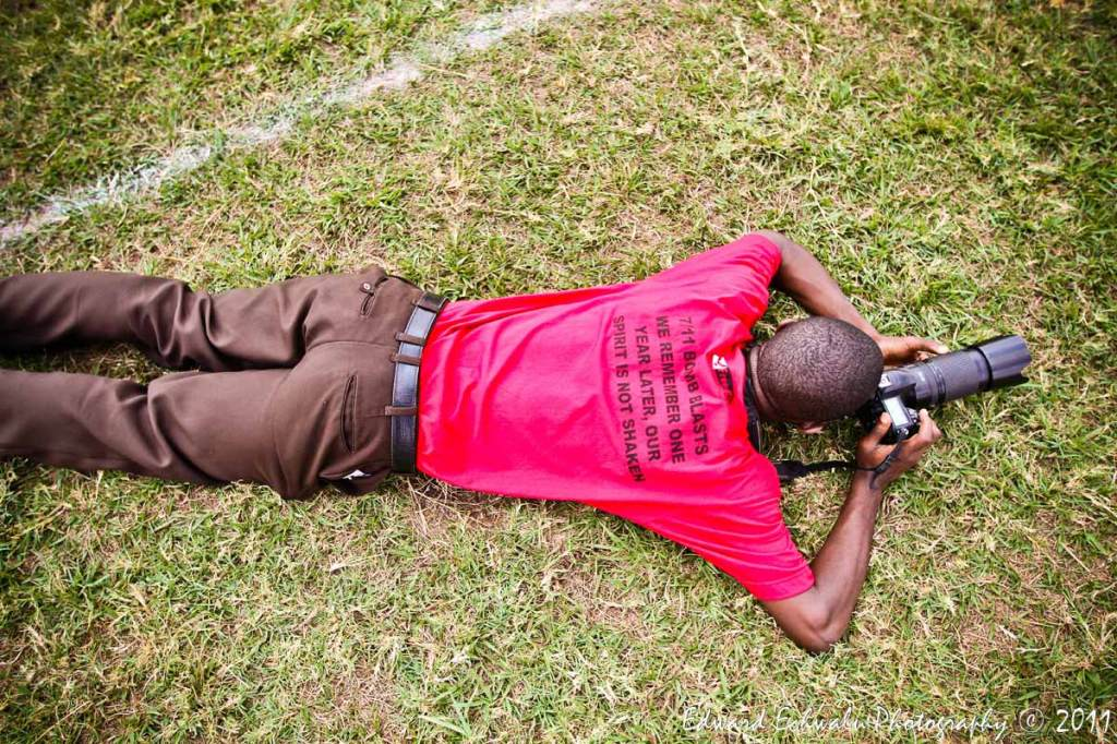 "A photojournalist lies on the ground while taking pictures at Kyadondo memorial prayers with words inscribed on his T-shirt reading; ""7/11 bomb blast, we remember one year later, our spirit is not shaken"