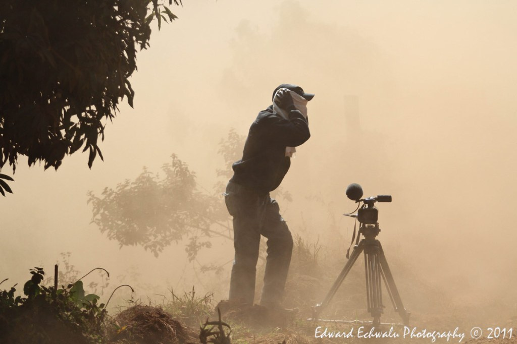 Justine Dralaze, a video journalist with Reuters covers his face amidst a cloud of dust after a rally car passed during the Pearl of Africa rally 2011