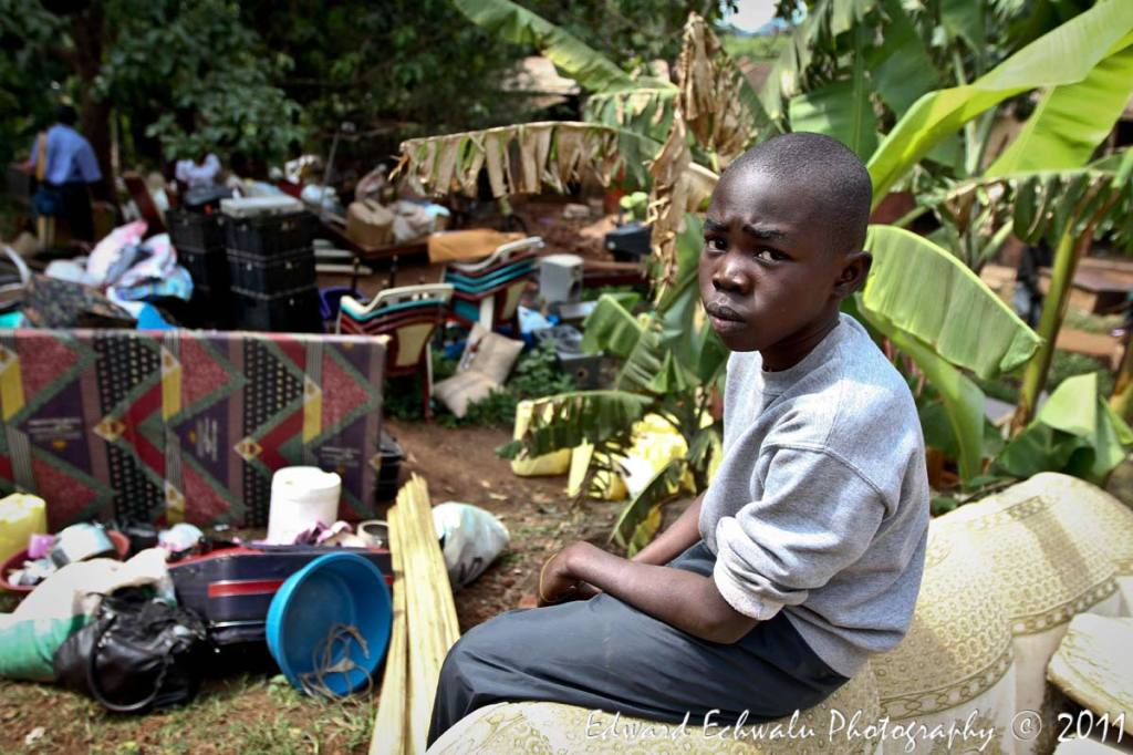 "Pius Lubangakene, a primary four pupil of Noble Junior School was instructed by his parents not to go to school to prepare for the eventuality that they are evicted. Here, he sits among their property after their house was run down by a grader on July 4, 2011. Asked where he would go now that they were forcefully evicted, Pius said, ""I don't know""."