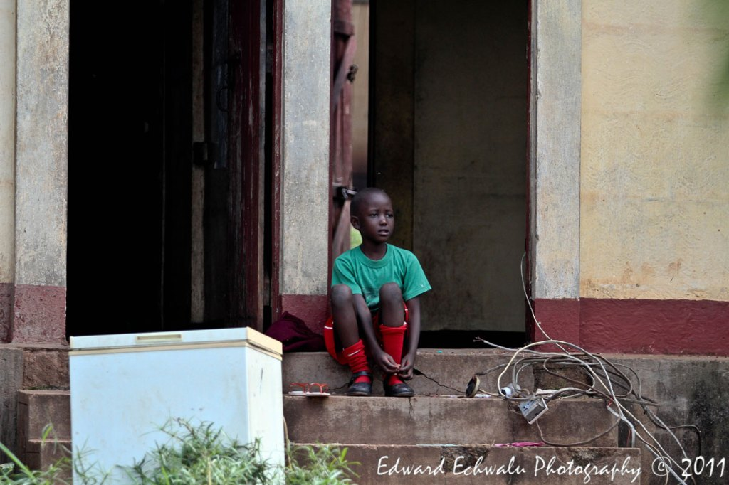 I got this little school boy in his full uniforms sitting right in front of their house as his elders run up and down the house clearing their property before the house is broken down on July 4, 2011. He looked confused, probably wondering what was happening. He too, did not go to school.