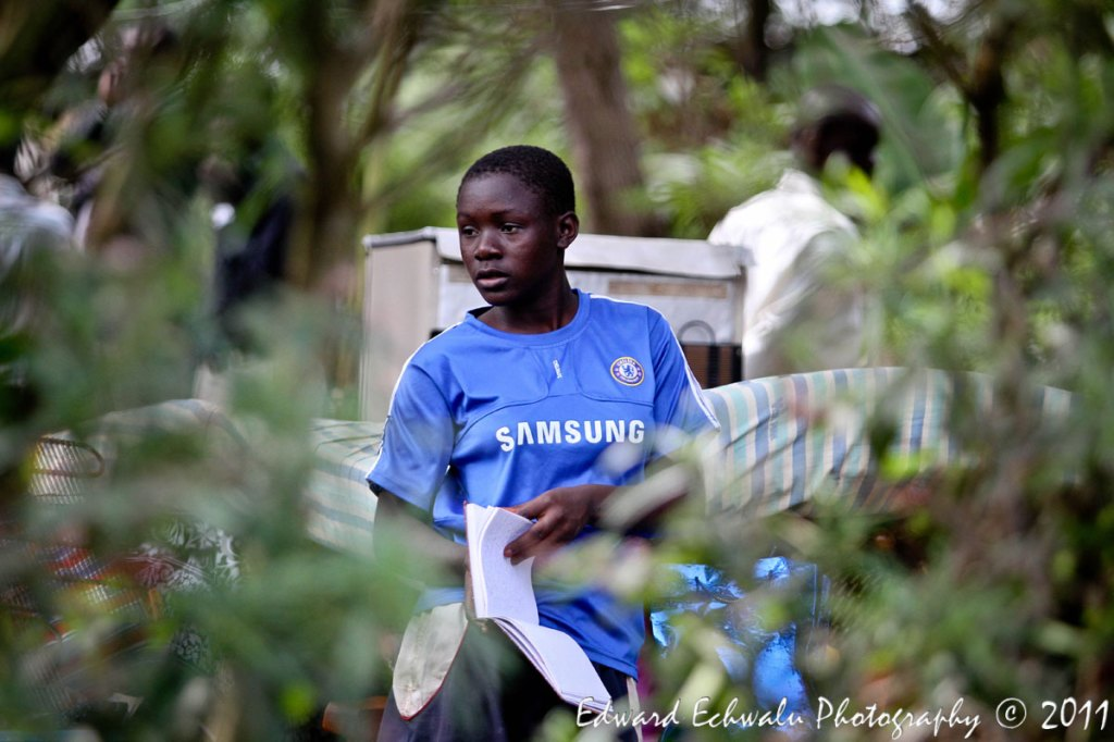 DISPLACED: A girl flips through pages of a book at their compound after their house was broken down on July 4, 2011. The eviction, Kampala City Council Authority (KCCA) says will pave way for the redevelopment of the area (Naguru/Nakawa estates) into a modern Satelite town.