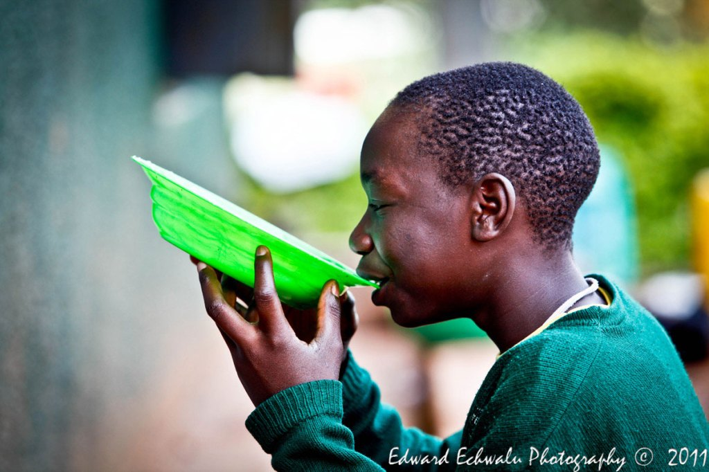 A pupil of Mengo Primary School takes porridge in a plastic plate during break time. Of about 128 million children enrolled in primary schools in Sub-Saharan Africa, few of them get anything to eat while at school. Many even go to school without breakfast.