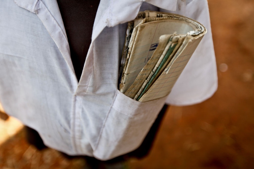 A pupil is seen carrying books in his pocket during a lunch break.Most of them cannot afford backpacks. Poverty still bites most of the pupils in the north as families recover from a 20year old LRA war.
