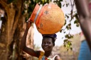 A woman carries a pot to the market in Lira district, north of Uganda's capital, Kampala. According to a UN report; In agriculture, sub-Saharan Africa's most vital economic sector, women contribute 60–80 per cent of labour in food production, both for household consumption and for sale. But while they do most of the work, they lack access to markets and credit. In Uganda, women make up 53 per cent of the labour force, but only sell 11 per cent of the cash crops.