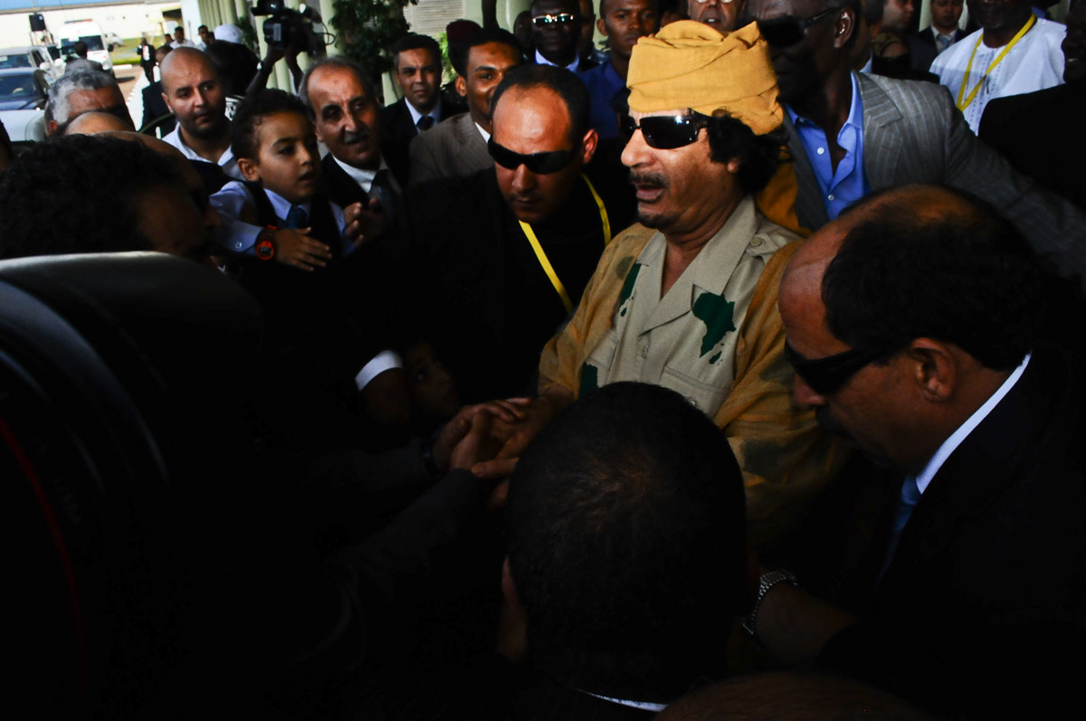 "Muammar Gaddafi arrives at the Entebbe International Airport for the 2010 AU Summit in Kampala on August 24, 2010. It happened to be his last visit to Uganda after being killed by Libyan forces with support from NATO.  ""We announce to the world that Gaddafi has been killed at the hands of the revolution,"" National Transitional Council (NTC) spokesman Abdel Hafez Ghoga said on Thursday in the eastern city of Benghazi."
