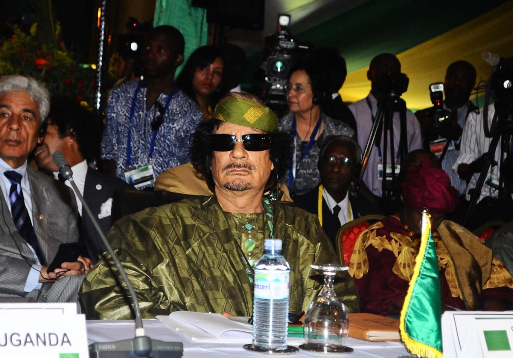 "Muammar Gaddafi arrives at the Entebbe International Airport for the 2010 AU Summit in Kampala on August 25, 2010. It happened to be his last visit to Uganda after being killed by Libyan forces with support from NATO.  ""We announce to the world that Gaddafi has been killed at the hands of the revolution,"" National Transitional Council (NTC) spokesman Abdel Hafez Ghoga said on Thursday in the eastern city of Benghazi."