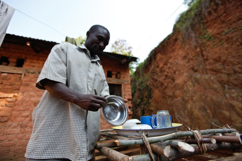 Zakalia, is seen washing utensils as his wife (not in the picture) did the cooking. Margaret says her husband's hand has taken of a lot of burden off her shoulders. Family revenues have increased as a result of the team work.