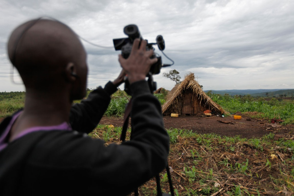 Justin Dralaze, a Reuters journalist films some of the makeshift houses built by the displaced communities after being forcefully and violently evicted by National Forestry Authority (NFA) and Police. Oxfam reports that Community members who had previously spoken to the international media say they have been singled out and questioned by NFC staff. New Forests Company (NFC) has been accused in a report by Oxfam to have caused the forceful displacement of 22,500 people in Kiboga and Mubende districts for them to plant trees as part of a lucrative scramble for arable land that can be used to satisfy the multi-billion dollar carbon trading ponzi scheme, which is worth $1.8 million a year to the company