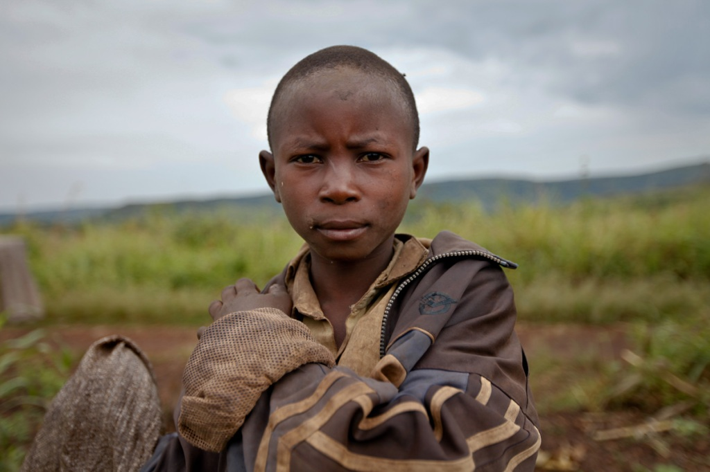 SCHOOL DROPOUTS: A displaced teenage farmer fresh from the garden in Mubende. Many in his age bracket have temporarily stopped going to school after being evicted from their homes. New Forests Company (NFC) has been accused in a report by Oxfam to have caused the forceful displacement of 22,500 people in Kiboga and Mubende districts for them to plant trees as part of a lucrative scramble for arable land that can be used to satisfy the multi-billion dollar carbon trading ponzi scheme, which is worth $1.8 million a year to the company